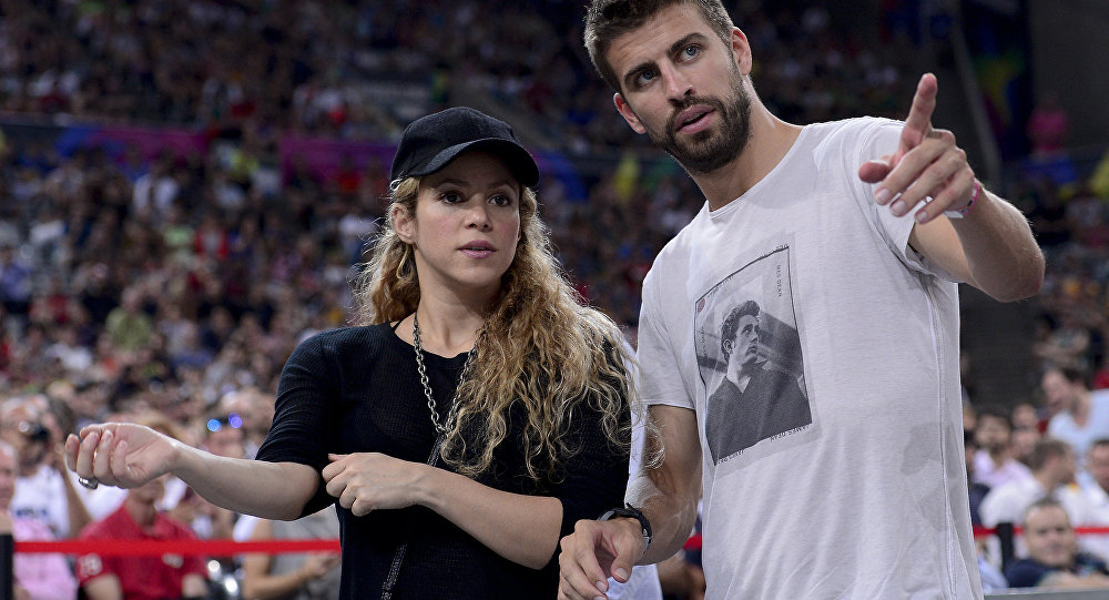 FC Barcelona's defender Gerard Pique (R) and his wife Colombian singer Shakira attend the 2014 FIBA World basketball championships quarter-final match Slovenia vs USA at the Palau Sant Jordi arena in Barcelona on September 9, 2014