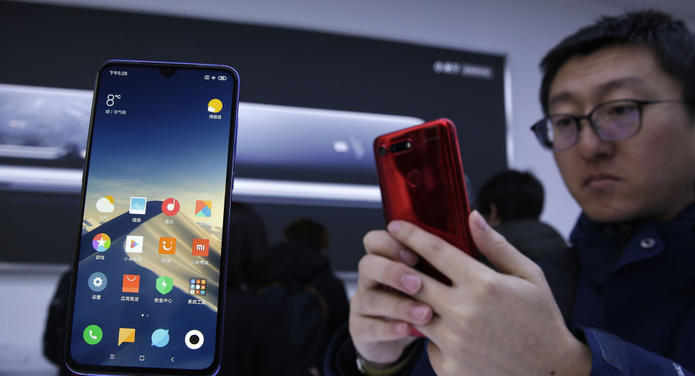 An invited guest takes a photo of Xiaomi new model Mi 9 displayed on an exhibition booth after its launch event in Beijing, Wednesday, Feb. 20, 2019