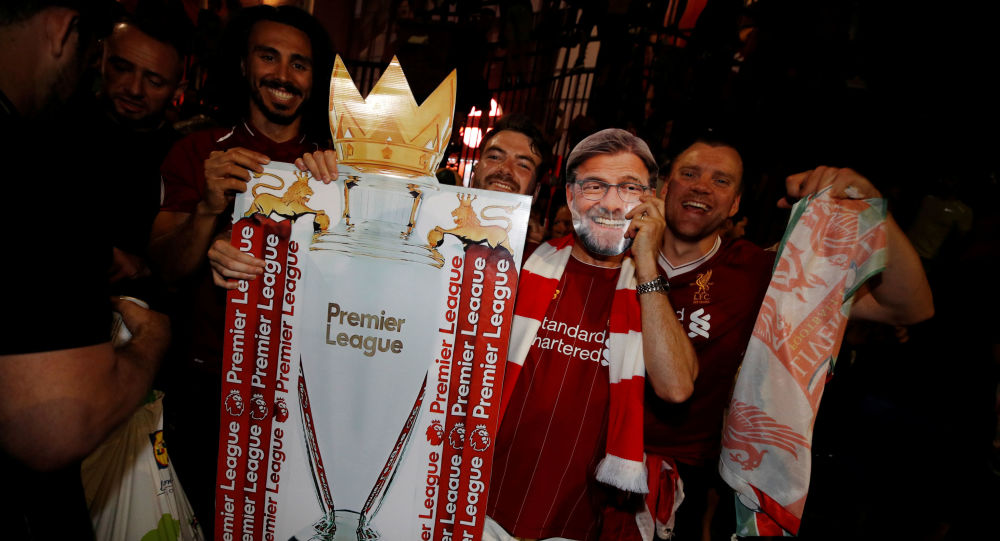 Liverpool fans - including one wearing a Jurgen Klopp mask - celebrate winning the Premier League for the first time