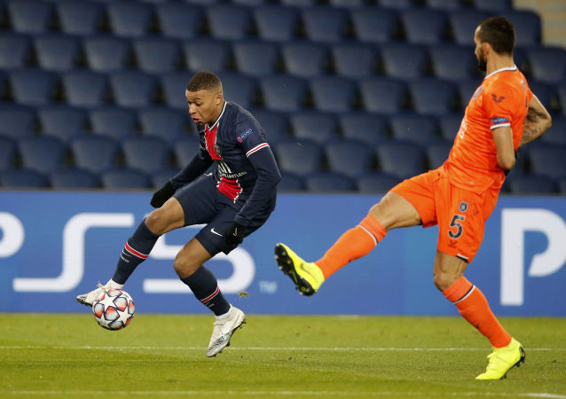 PSG's Kylian Mbappe,left,t,controls the ball next to Basaksehir's Mehmet Topal, during the Champions League group H soccer match between Paris Saint Germain and Istanbul Basaksehir at the Parc des Princes stadium in Paris, Tuesday Dec. 8 , 2020.