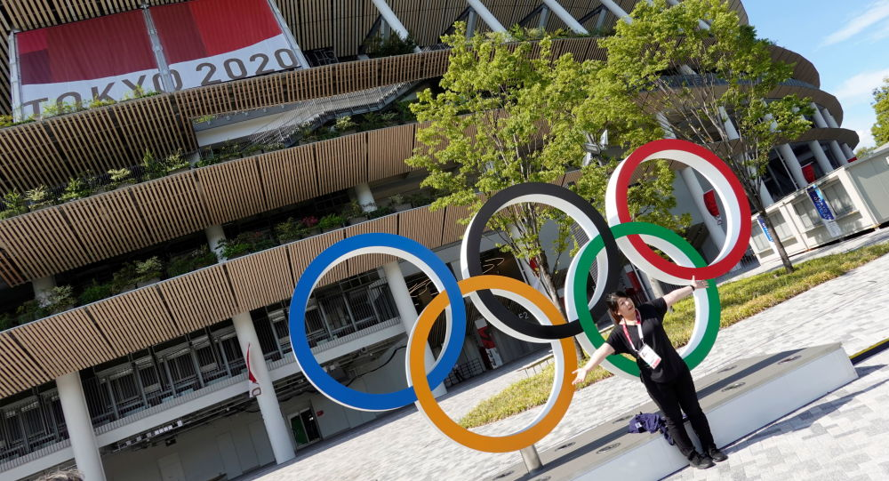 A woman poses in front of the National Stadium, the main stadium of Tokyo 2020 Olympics and Paralympics in Tokyo, Japan July 23, 2021.