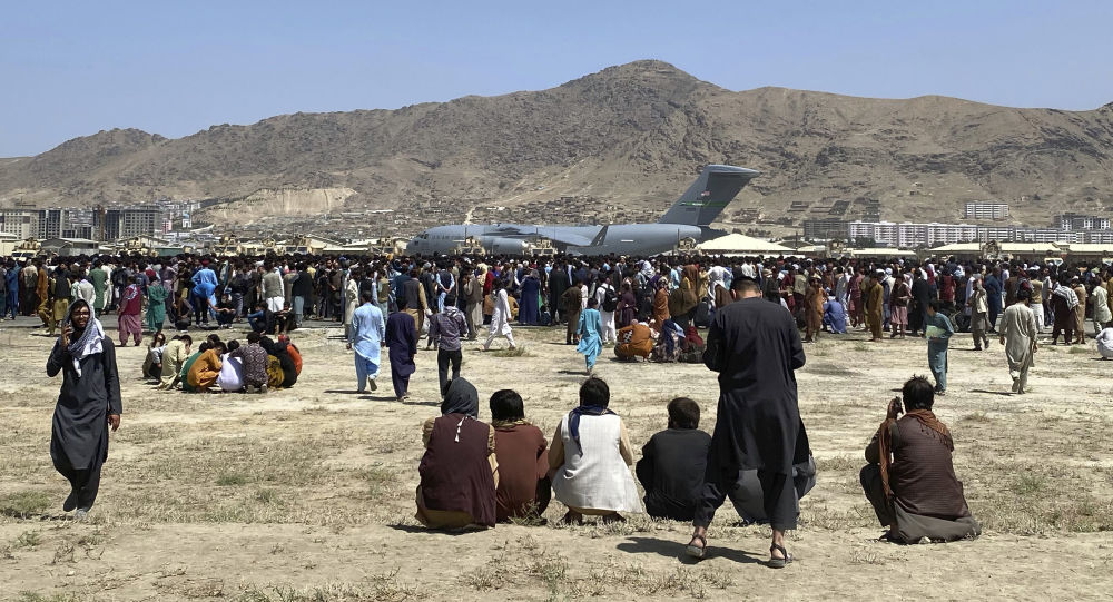 Hundreds of people gather near a U.S. Air Force C-17 transport plane at a perimeter at the international airport in Kabul, Afghanistan, Monday, Aug. 16, 2021