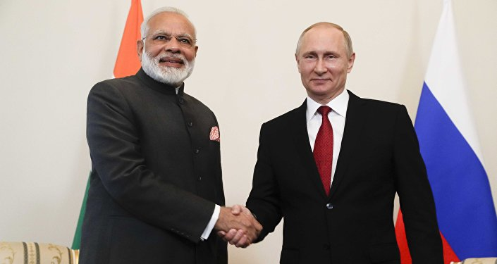Russian President Vladimir Putin (R) shakes hands with Indian Prime Minister Narendra Modi during a meeting on the sidelines of the St. Petersburg International Economic Forum (SPIEF), Russia