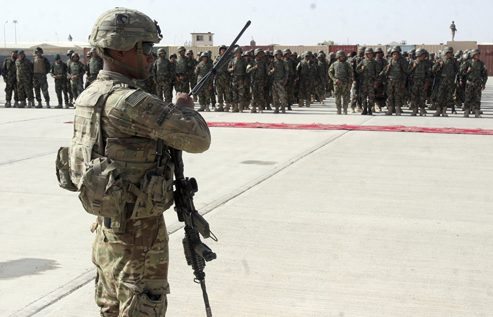 US military personal stands guard during a graduation ceremony for Afghan troops, in Lashkargah