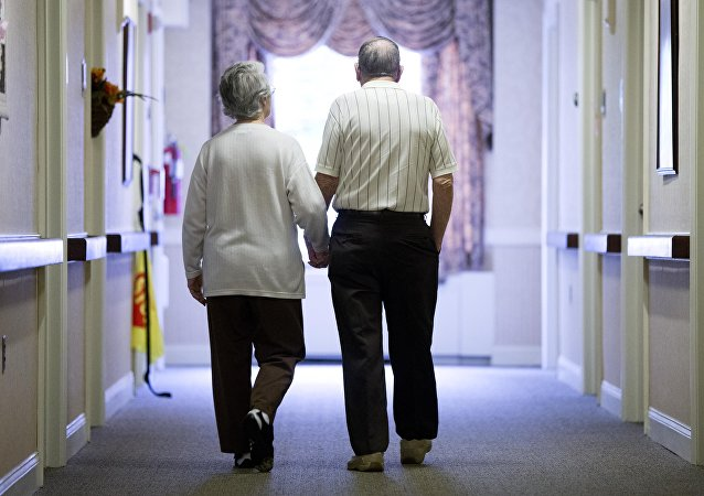 Decima Assise, who has Alzheimer's disease, and Harry Lomping walk the halls, Friday, Nov. 6, 2015, at The Easton Home in Easton, Pa