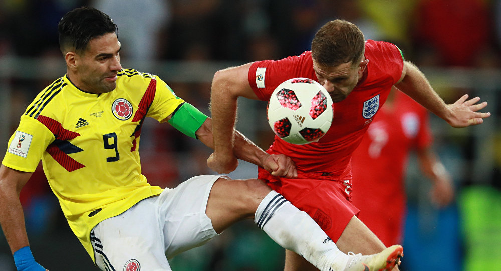 Colombia's Radamel Falcao, left, struggles for a ball with unidentified England's player during extra time of the World Cup Round of 16 soccer match between Colombia and England, at the Spartak Arena, in Moscow, Russia, July 3, 2018.