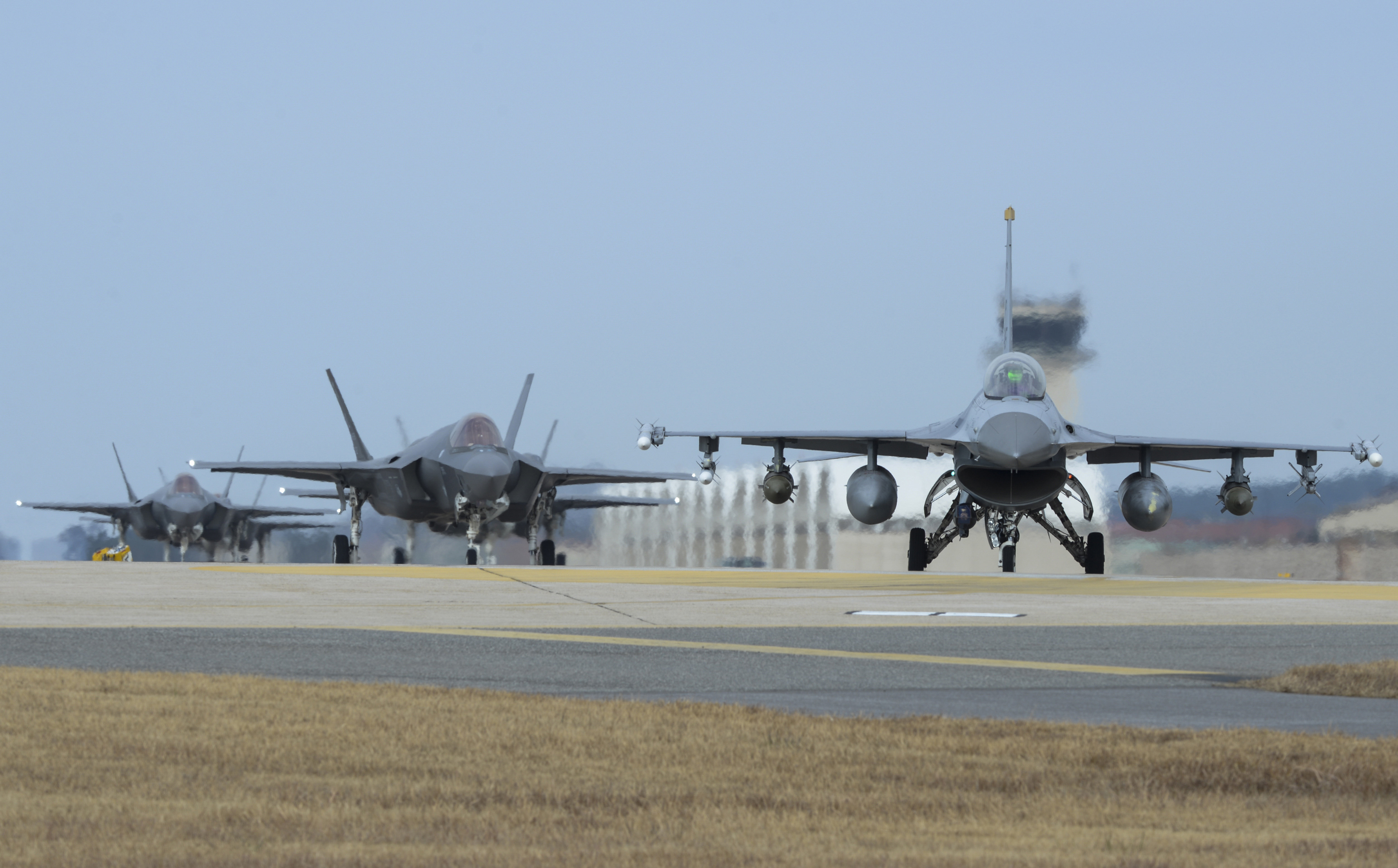 U.S. Air Force F-16 Fighting Falcon, right, and F-35A Lightning IIs assigned to the 34th Expeditionary Fighter Squadron Hill Air Force Base, Utah, taxi toward the end of the runway during the exercise VIGILANT ACE 18 at Kunsan Air Base, South Korea