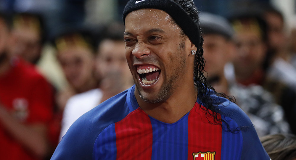 Former FC Barcelona player Ronaldinho, laughs as he enters the stadium during a friendly soccer match between the FC Barcelona and Real Madrid Legends, at the Camille Chamoun Sports City in Beirut, Lebanon, Friday,