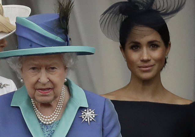 Britain's Queen Elizabeth II, Camilla the Duchess of Cornwall, left, and Meghan the Duchess of Sussex walk out onto the balcony to watch a flypast of Royal Air Force aircraft pass over Buckingham Palace in London, Tuesday, July 10, 2018.