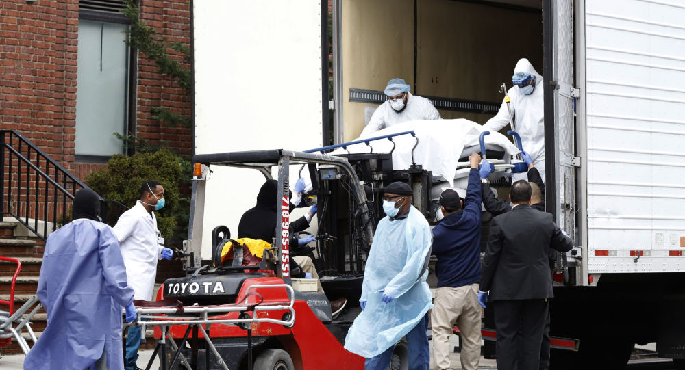 Workers load deceased person into truck trailer outside Brooklyn Hospital Center during the coronavirus disease (COVID-19) in New York