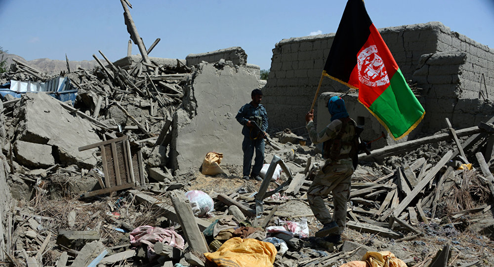 Afghan security force member walks holding the Afghan national flag after government forces took full control of a village from Islamic State (IS) fighters during a military operation in Kot District of eastern Nangarhar province (File)