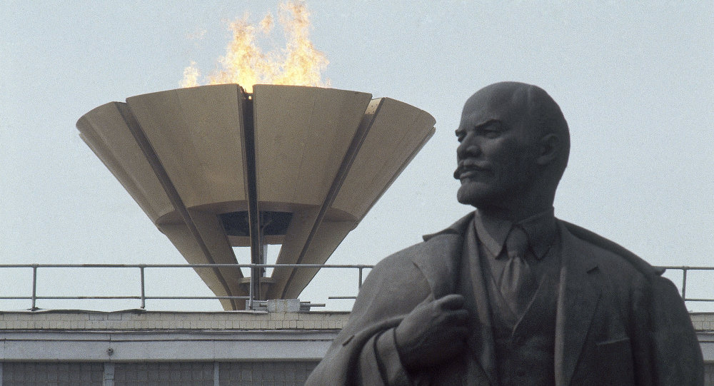 The Olympic flame rises over statue of Lenin outside Lenin Stadium in Moscow during the 1980 Olympic Games